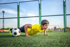 Azjatycki chłopiec nastolatek robi Ups od podłoga na zielonym gazonie Youn obrazy royalty free