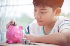 Azjatycki chłopiec oszczędzania pieniądze w różowym prosiątko banku Zdjęcia Stock