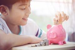 Azjatycki chłopiec oszczędzania pieniądze w różowym prosiątko banku Fotografia Royalty Free