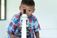 Azjatycki chłopiec use mikroskop w lab dla badania obrazy stock