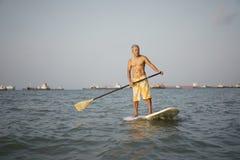 Azjatycki chińczyk przechodzić na emeryturę surfing w morzu Zdjęcia Stock