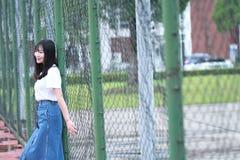 Azjatycki Chiński student uniwersytetu cieszy się czas wolnego przy kampusem Fotografia Stock