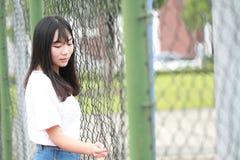 Azjatycki Chiński student uniwersytetu cieszy się czas wolnego przy kampusem Obrazy Stock