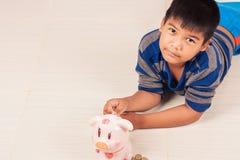 Azjatycki chłopiec oszczędzania pieniądze w piggybank Zdjęcia Royalty Free