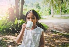 Azjatycki dzieciak pije salową, naturalną zieleń, Obrazy Stock