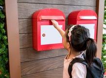 Azjatycki dzieciak wysyła jej poczta w czerwonej metal skrzynce pocztowa obrazy royalty free