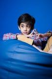 Azjatycki dzieciaka obsiadanie na bobowej torbie z ręka przodem Ostrość na rękach Zdjęcie Stock