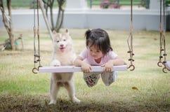 Azjatycki dziecka dziecko na huśtawce z szczeniakiem Fotografia Royalty Free