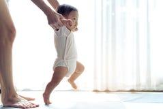 Azjatycki dziecko bierze pierwszego kroka spacer naprzód na miękkiej części macie zdjęcia royalty free