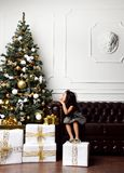 Azjatycki dziecko dziewczynki dzieciaka obsiadanie pod dekorującą złocistą choinką z złocistymi patchworku prezenta teraźniejszoś fotografia stock