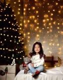 Azjatycki dziecko dziewczynki dzieciaka obsiadanie pod dekorującą złocistą choinką z złocistymi patchworku prezenta teraźniejszoś zdjęcie stock