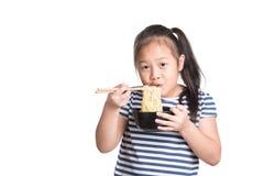 Azjatycki dziecko dziewczyny wiek 7 rok, je Natychmiastowych kluski na białym b obraz stock