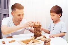 Azjatycki dziecko i ojciec bawić się z drewnianymi blokami w pokoju w domu Jakby edukacyjne zabawki dla preschool i dziecina zdjęcia stock