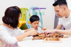 Azjatycki dziecko i rodzice bawić się z drewnianymi blokami w pokoju w domu Jakby edukacyjne zabawki dla preschool i dziecina fotografia stock