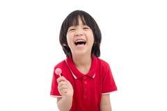 Azjatycki dziecko je lizaka na białym tle Fotografia Royalty Free