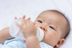 Azjatycki dziecko niemowlak cieszy się wodę pitną od butelki Zdjęcie Royalty Free