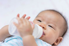 Azjatycki dziecko niemowlak cieszy się wodę pitną od butelki Zdjęcia Royalty Free
