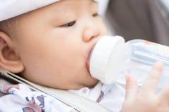 Azjatycki dziecko niemowlak cieszy się wodę pitną od butelki Fotografia Royalty Free