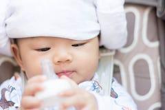 Azjatycki dziecko niemowlak cieszy się wodę pitną od butelki Obrazy Stock