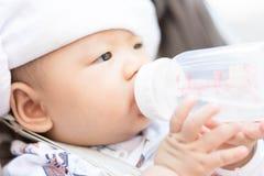 Azjatycki dziecko niemowlak cieszy się wodę pitną od butelki Zdjęcia Stock