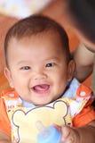 Azjatycki dziecko ono uśmiecha się szczęśliwie i butelkę mleko w ręce Obrazy Royalty Free