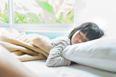 Azjatycki dziewczyny dosypianie na łóżku zakrywającym z koc Zdjęcia Royalty Free
