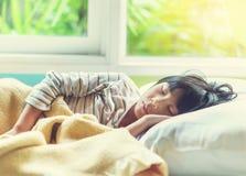 Azjatycki dziewczyny dosypianie na łóżku zakrywającym z koc Zdjęcie Royalty Free