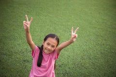 Azjatycki dziewczyny ` s uśmiech i być usytuowanym patrzeje na sztucznej trawy zdjęcia royalty free