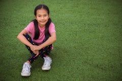 Azjatycki dziewczyny ` s uśmiech i być usytuowanym patrzeje na sztucznej trawy zdjęcia stock