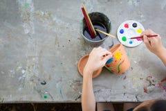 Azjatycki dziewczyny studiowanie, uczenie i sztuka dzieciak używa paintbrush malować wodnego kolor na doniczkowej roślinie robić  zdjęcie royalty free