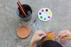 Azjatycki dziewczyny studiowanie, uczenie i sztuka dzieciak używa paintbrush malować wodnego kolor na doniczkowej roślinie robić  fotografia royalty free