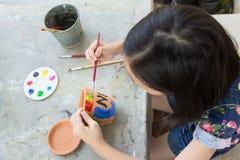Azjatycki dziewczyny studiowanie, uczenie i sztuka dzieciak u?ywa paintbrush malowa? wodnego kolor na doniczkowej ro?linie robi?  obrazy royalty free
