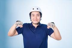 Azjatycki faceta gest jechać na rowerze bicykl, z rowerowym hełmem i rękawiczkami Obrazy Stock