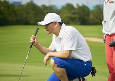 Azjatycki golfisty przycupnięcie w pola golfowego celowaniu i narządzanie dla stawiać Zdjęcie Royalty Free