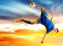 Azjatycki gracz futbolu mężczyzny doskakiwanie i kopanie piłka w powietrzu obraz stock