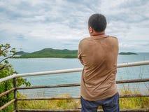 Azjatycki Gruby podróżnika stojak na punkt widzenia z tropikalnym idyllicznym oceanem i bielu obłocznym niebem w urlopowym czasie zdjęcie stock