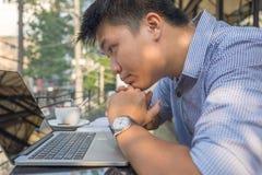 Azjatycki inwestor ogląda zmianę rynek papierów wartościowych na laptopie obrazy stock