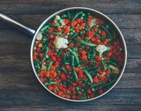 Azjatycki karmowy naczynie jarzynowa mieszanka marchewki, grochy, fasolki szparagowe i kalafior w smażyć nieckę na starym drewnia Obrazy Stock