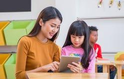 Azjatycki kobieta nauczyciel uczy dziewczyna ucznia z pastylka komputerem w sali lekcyjnej przy dziecina preschool, Online edukac zdjęcia stock