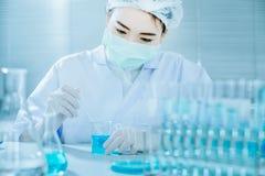 Azjatycki kobieta naukowiec z próbną tubką robi badaniu w klinicznym laboratorium Zdjęcia Royalty Free