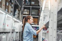 Azjatycki kobieta pracownik pracuje z cyfrowej pastylki sprawdza pudełkami importa i eksporta Logistycznie dostaw pakunki w magaz obraz stock
