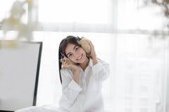 Azjatycki kobieta uśmiechu odczucie beztroski i ona kłama na łóżku w ranku po budzić się, up młoda piękna dziewczyny i słuchający Fotografia Stock