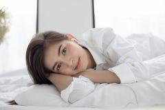 Azjatycki kobieta uśmiechu odczucie beztroski i ona kłama na łóżku w ranku po budzić się, up młoda piękna dziewczyny i słuchający Zdjęcia Stock