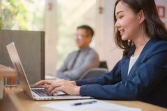 Azjatycki kobieta urzędnik jest pracujący na laptopie z cieszy się i szczęśliwy w biurze fotografia stock