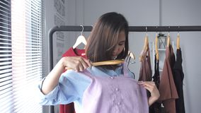 Azjatycki kobieta zakupy odziewa Kupujący patrzeje odzież na poręczu indoors w sklepie odzieżowym zbiory