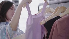 Azjatycki kobieta zakupy odziewa Kupujący patrzeje odzież na poręczu indoors w sklepie odzieżowym zdjęcie wideo