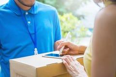 Azjatycki kobiety akceptować otrzymywa dostawę pudełka od doręczeniowego azjatykciego mężczyzna zdjęcia royalty free