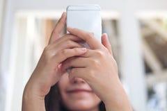 Azjatycki kobiety mienie, używać mądrze telefon pokrywę i patrzejący jej twarz zdjęcie stock