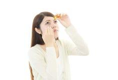 Azjatycki kobiety obcieknięcia oko z oko kroplami obraz stock