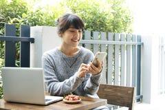 Azjatycki kobiety obsiadanie przy używać w domu smartphone i stołem Typ zdjęcie stock